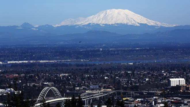 Mount St. Helens, and Mount Rainier beyond to the north, rises above Portland and Vancouver, Washington.