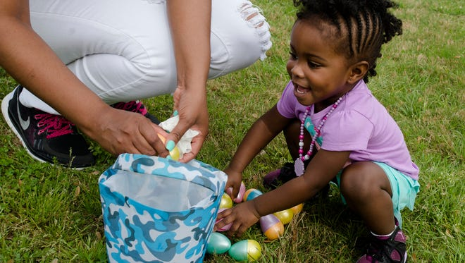 Carson Neolmds, 2, smiles as she goes through her eggs during the annual Easter Egg hunt set up by Montgomery Sheriff Department at Auburn University in Montgomery, Saturday, March 26, 2016, in Montgomery, Ala.