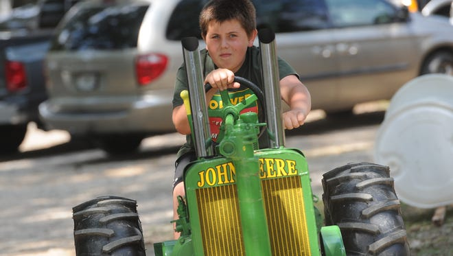In this file photo, a young man rides his John Deere replica through the parking lot, at the 2014 Olde Tyme Days event in Fawn Grove.