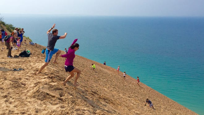 A couple takes a leap of faith Aug. 31, 2015, at Michigan's iconic Sleeping Bear Dunes in Empire, Mich. Visitors walk part of the giant dune along Pierce Stocking Drive.