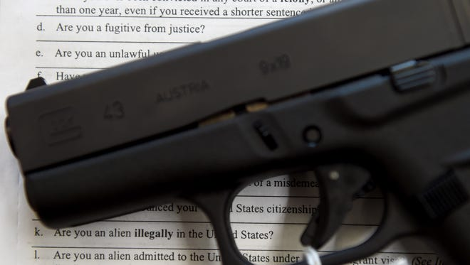 In this file photo, a handgun sits on top of a form used for firearms transactions.