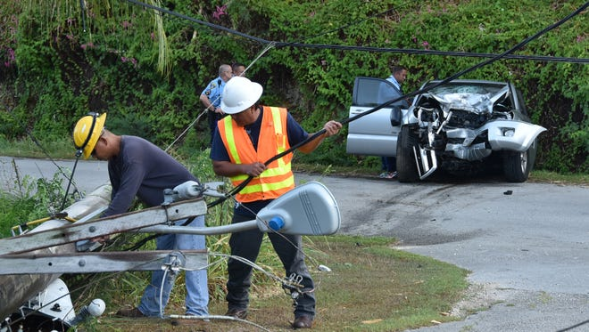 Guam Police Department Highway Patrol Division officers investigate an auto-pole crash on Toto Canada Road on Tuesday, May 17. Guam Power Authority personnel prepared to replace a damaged pole to restore power in the area.