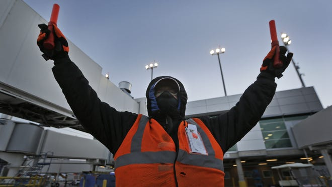 In this Nov. 13, 2014 photo, dressed for the cold, Southwest Airlines ground crew worker Johnny Matlock directs an early morning flight arriving into a gate at Love Field in Dallas.
