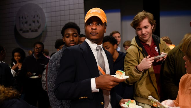 Montgomery Bell Academy football player Ty Chandler hands out cake to his classmates after signing his letter of intent to attend the University of Tennessee during a ceremony at Wednesday in Nashville.