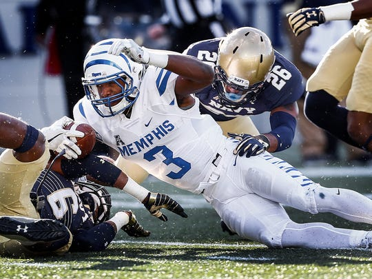 University of Memphis receiver Anthony Miller (middle) reaches for a first down against the Navy defense during second quarter action at Navy-Marine Corps Memorial Stadium in Annapolis, Maryland.