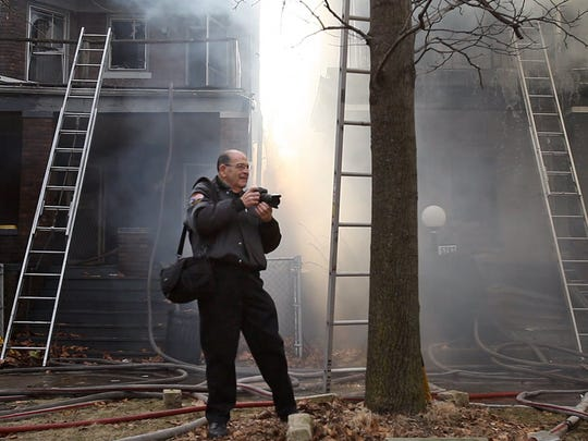 Bill Eisner photographs firefighters at work during a blaze on Detroit's west side in 2011.
