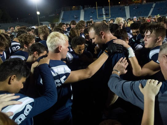 Reitz Head Coach Andy Hape prays with his team after