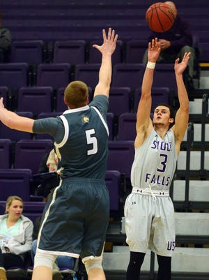 USF's Mack Johnson shoots for three over Southwest Minnesota State's Mitch Weg in Tuesday's game at the Stewart Center, Dec 8, 2015.