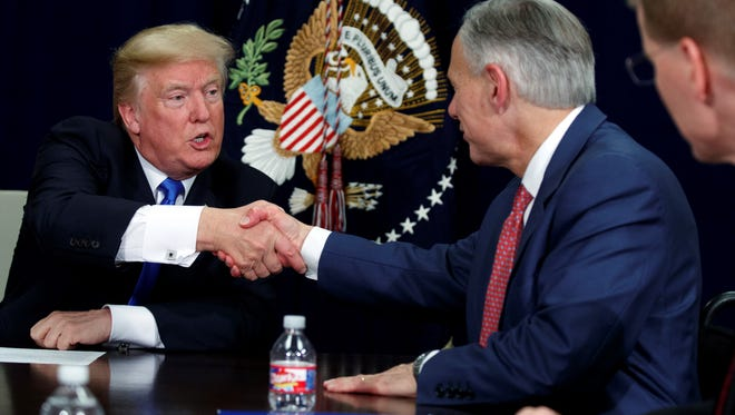 President Donald Trump shakes hands with Texas Gov. Greg Abbott during a briefing on hurricane recovery efforts, Wednesday, Oct. 25, 2017, in Dallas.