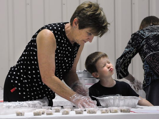 Paul Hoelscher, 4, makes a spontaneous face while helping his grandmother Dot spoon bread pudding into cups, courtesy of St. Mary's Catholic Church, for the Taste of Ballinger Tuesday Feb. 21, 2017. The fundraiser benefited the Ballinger Carnegie Library.
