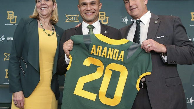 """Baylor President Dr. Linda A. Livingstone, left, and athletic director Mack Rhoades, right, present new head football coach Dave Aranda with a """"20"""" jersey during his introductory news conference on Jan. 20."""