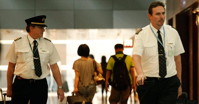 Two pilots from Cathay Pacific walk in the Hong Kong International Airport in November 2011.