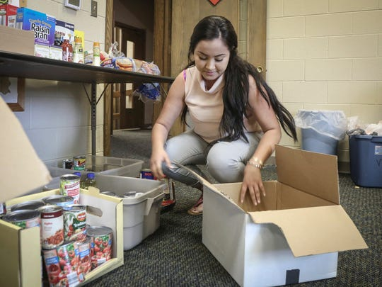 Cindy Delgado of Mount Pleasant packs food goods into care packages for families affected by the May 9 ICE raid that resulted in the arrests of more than 30 employees at the Midwest Precast Concrete facility in Mount Pleasant.
