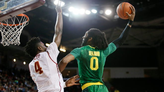 Oregon's Dwayne Benjamin, right, dunks the ball over Southern California's Chimezie Metu, left, during the first of an NCAA college basketball game, Saturday, March 5, 2016, in Los Angeles.