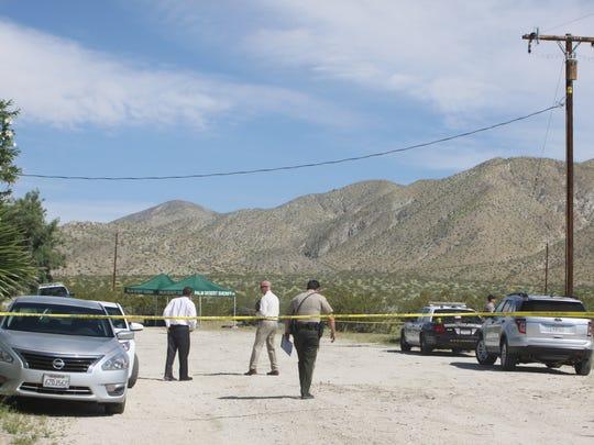 Riverside County sheriff's investigators convene next to a field where a deputy shot an assault suspect Sunday near Desert Hot Springs.