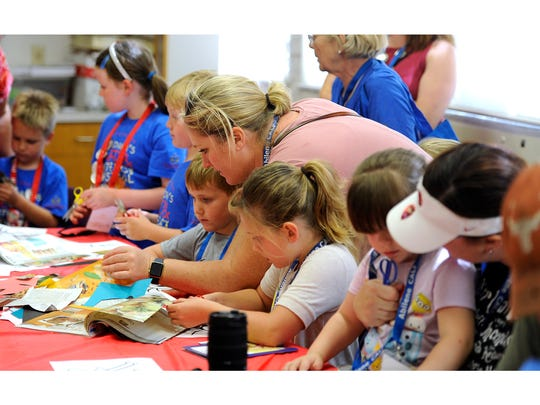 Kate Haney (top center) helps her son, Tom, 5, and daughter, Caroline, 7, with their art project at the National Center for Children's Illustrated Literature during the Children's Art & Literacy Festival on Saturday, June 10, 2017, in downtown Abilene.