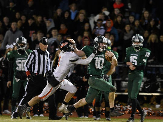 New Milford's Matt McElroy fights off a tackle as he runs for a first down in 2017.