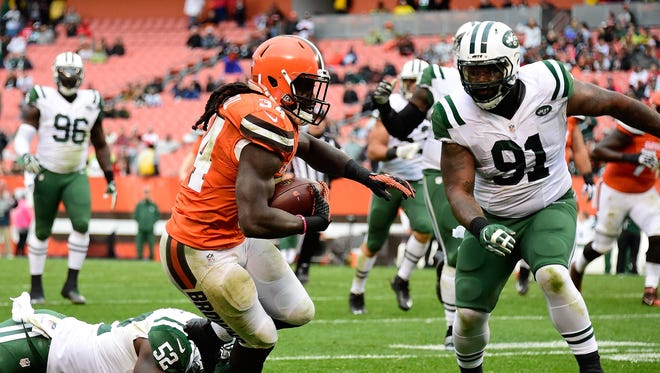 Isaiah Crowell #34 of the Cleveland Browns carries the ball in front of the defense of David Harris #52 and Sheldon Richardson #91 of the New York Jets at FirstEnergy Stadium on October 30, 2016 in Cleveland, Ohio.