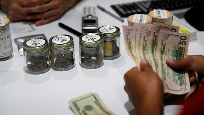 A person buys marijuana at the Essence cannabis dispensary in Las Vegas. Many employers across the country are quietly taking what once would have been a radical step: They're dropping marijuana from the drug tests they require of prospective employees.