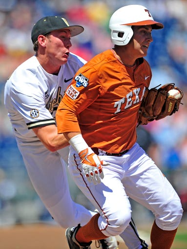 Texas' Mark Payton, right, is tagged by Vanderbilt pitcher Brian Miller at first in the College World Series at TD Ameritrade Park in Omaha, Neb., Friday, June 20, 2014. Miller dropped the ball after tagging Payton on the play. Vanderbilt lost 4-0.