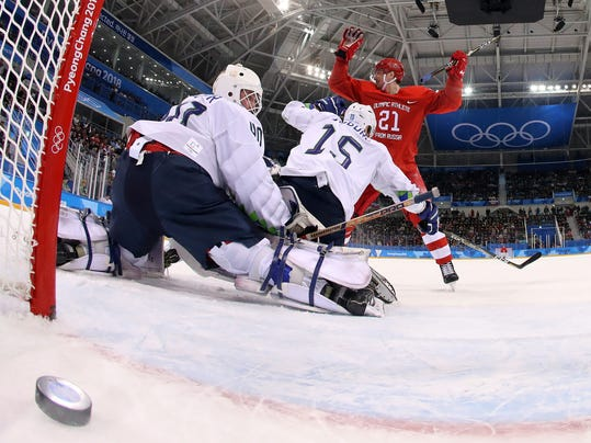 Russian athlete Sergei Kalinin (21) reacts as Sergei Mozyakin scores a goal against goalie Luka Gracnar (40), of Slovenia, during the first period of the preliminary round of the men's hockey game at the 2018 Winter Olympics in Gangneung, South Korea, Friday, Feb. 16, 2018. (Jamie Squire/Pool Photo via AP)
