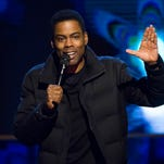 Academy Awards producer Reginald Hudlin says host Chris Rock is hard at work rewriting his material for next month's Oscar show.
