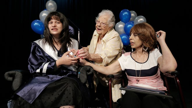 Del Valle High School held an impromptu graduation for special needs senior Jackie Avalos, left, in the school's theater Friday. Jackie's mother, Elva Avalos, right, who is terminally ill, had one wish: to see her daughter graduate. Doctors didn't think the hospice patient would live to see Jackie graduate if she participated with the rest of the school on June 8. Jackie and Elva Avalos were joined by Jackie's grandmother, Irene Rocha, center, on stage.