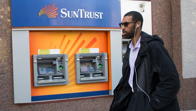 A man walks past a SunTrust bank ATM Oct. 11, 2016 in Washington, DC.