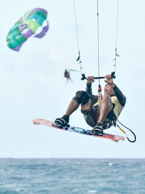 Kite surfer Rob Maunel catches air to rival a parasailer in Hagåtña on Dec. 31. Manuel said he chose this location to honor the watersports landmark Hagåtña Boat Basin, and to get in one last ride of the year.