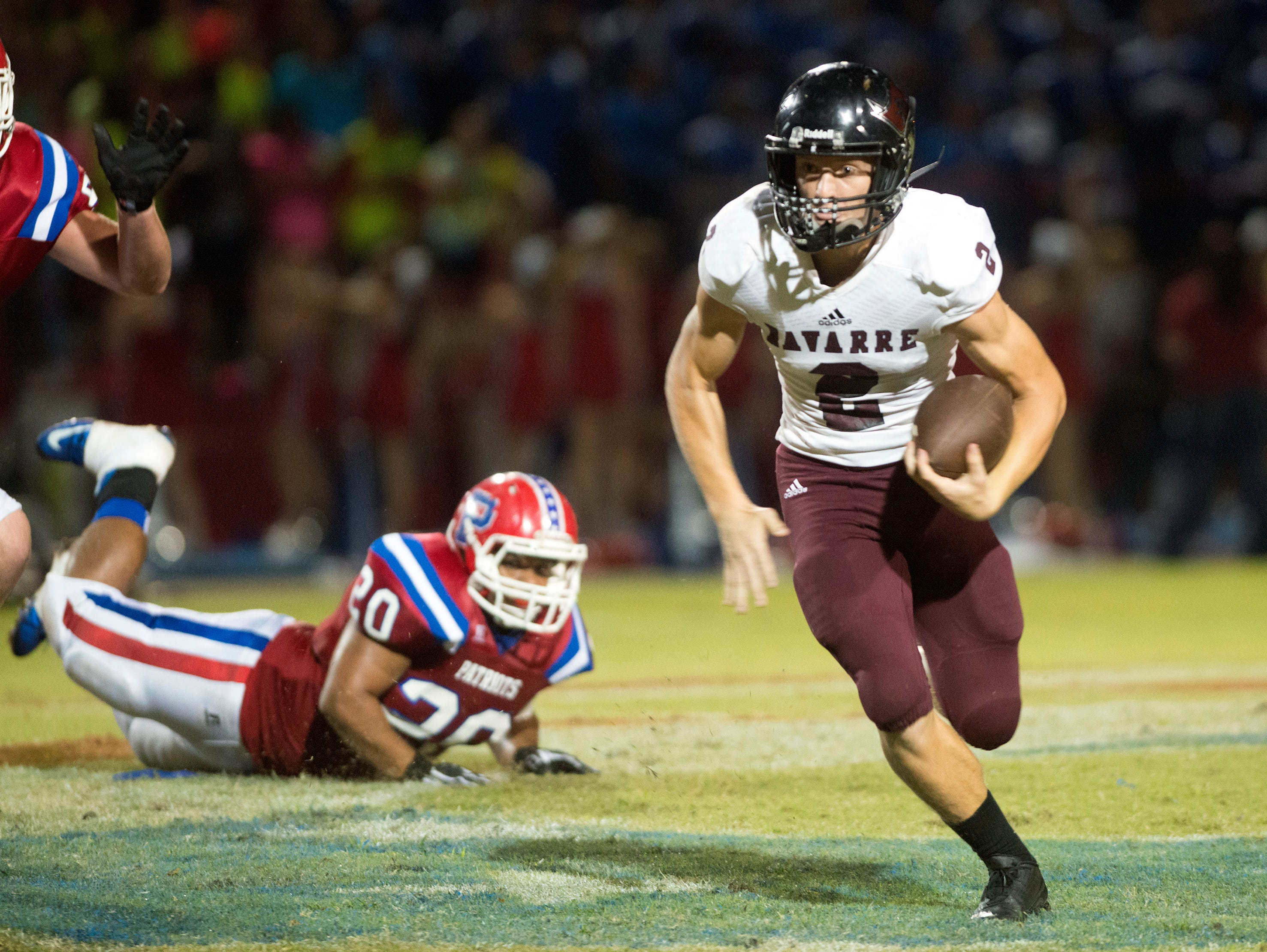 Navarre High School quarterback, Caine Adamson, (No. 2) slips out of the packet to runs for 1st down against the Pace High School defense during Friday night's District 2-6A game.