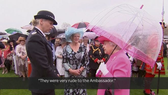 In image made from pool video, Queen Elizabeth II speaks with Scotland Yard Commander Lucy D'Orsi in the garden of Buckingham Palace in London, Tuesday, May 10, 2016.