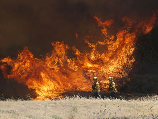 A hillside erupts in flame as a wildfire burns in Placerita Canyon in Santa Clarita, Calif., Monday, July 25, 2016. The smoky fire tore through drought-ravaged brush that hadn't burned in decades amid a sweltering heat wave and exploded over the weekend. (AP Photo/Nick Ut)