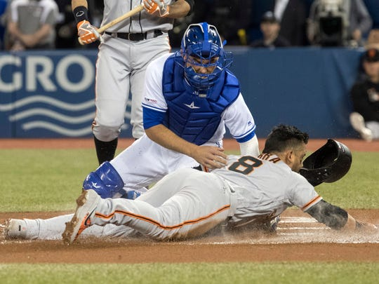 San Francisco Giants Gerardo Parra is out stealing home plate as Toronto Blue Jays catcher Luke Maile applies the tag during the first inning of a baseball game, Tuesday, April 23, 2019 in Toronto. (Fred Thornhill/Canadian Press via AP)