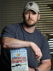 "Kyle poses with his best-selling book, ""American Sniper."""