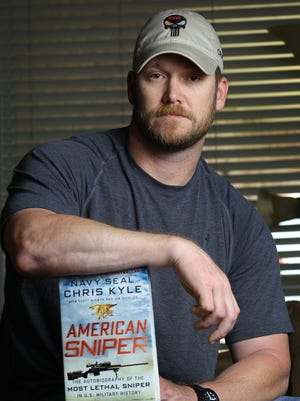 """Chris Kyle poses with his best-selling book, """"American Sniper."""""""
