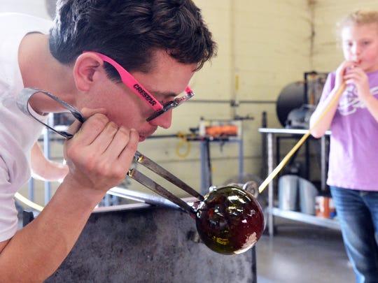 Glassblower Seth Hendrick keeps a close eye on the