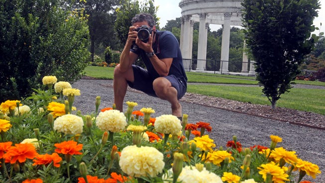 The Journal News/lohud photojournalist Seth Harrison takes a photo Friday at Untermyer Park in Yonkers.