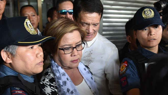 Philippine Senator Leila De Lima (C), a top critic of President Rodrigo Duterte, is pictured being escorted by police officers and her lawyer after her arrest at the Senate in Manila, Philippines.