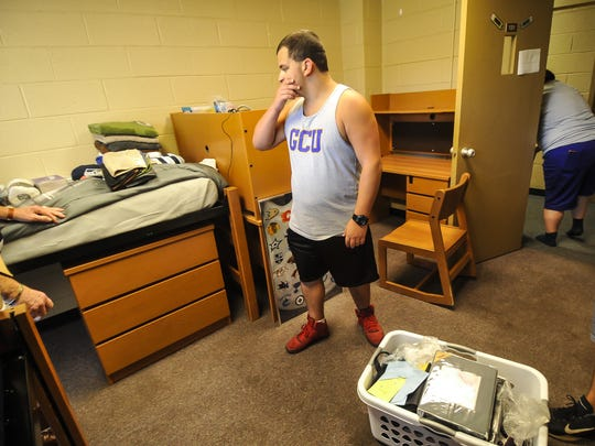 Joseph Lacasale contemplates what to unpack next during moving in day at Georgian Court University in Lakewood on Aug, 24. Joe along with his twin brother Anthony and twin sister Stepanie are three of four Quadruplets attending Georgian Court University this school year.