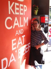 "Dayna Haupt, owner of Dayne's Chicago Beef & Dawgs in Thousand Oaks, poses next to the ""Keep Calm and Eat Da' Beef"" sign in the dining room of the fast-casual restaurant."