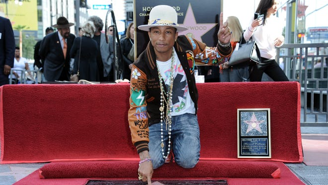 Pharrell Williams poses on his new star at the ceremony honoring him on the Hollywood Walk of Fame on Thursday, Dec., 04, 2014, in Los Angeles.