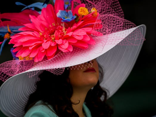 A woman wear a colorful hat watches a race on Derby