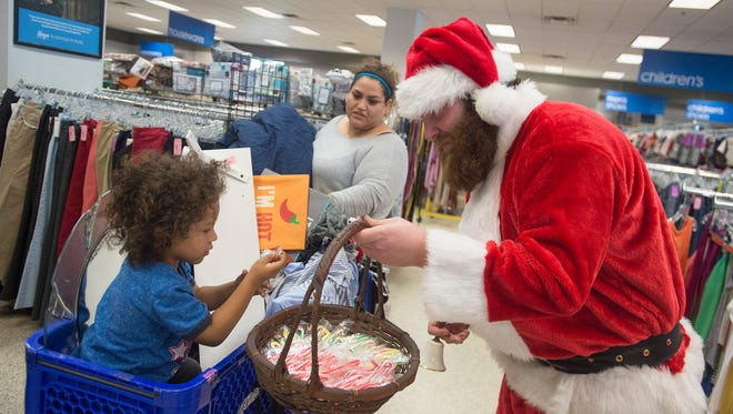 Kale Burnham delivers candy canes to children like Alexander Sarelleno, 3, dressed as Santa Claus at Goodwill in Fort Collins in this file photo from Saturday, December 9, 2017.