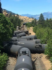 In this photo provided by Silas Bleakley, tank cars, carrying oil, are derailed Friday, June 3, 2016, near Mosier, Ore. The accident happened just after noon about 70 miles east of Portland. It involved numerous cars filled with oil, and one was burning. Highway 84 was closed for a 23-mile stretch between The Dalles and Mosier and the radius for evacuations was a half-mile. (Silas Bleakley via AP)