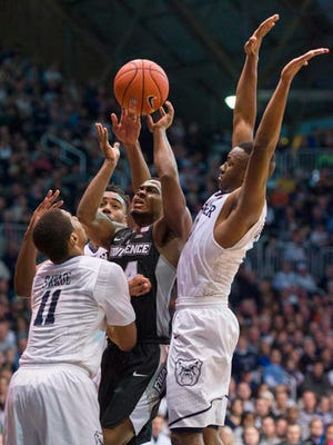 Providence guard Kyron Cartwright (24) shoots while being defended by Butler guard Kethan Savage (11), guard Avery Woodson (0) and forward Kelan Martin (30) during the second half of an NCAA college basketball game in Indianapolis, Sunday, Jan. 1, 2017. Butler won 78-61. (AP Photo/Doug McSchooler)