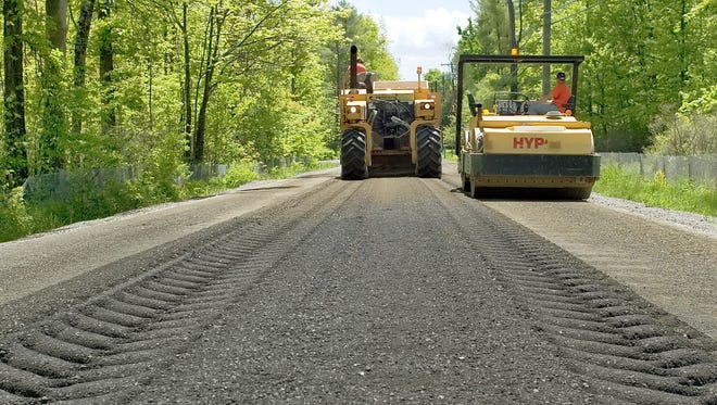 Sapsucker Woods Road in the Town of Dryden, shown being paved in 2005, was formerly known as Town Line Road.