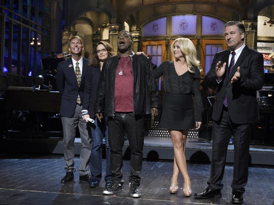 """In this Saturday, Oct. 17, 2015, photo, provided by NBC, comedians Jack McBrayer, from left to right, Tina Fey, Tracy Morgan, Jane Krakowski, and Alec Baldwin stand on stage during a monologue on the show, in New York. Morgan returned to a familiar stage, hosting """"Saturday Night Live"""" in his first appearance on the show since a vehicle crash that left him in a coma."""