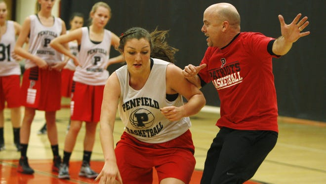 Penfield's Margot Hetzke, left, drives to the basket on coach Mark Vogt, right, during the team's practice at Penfield High School on Wednesday, Dec. 4, 2013.