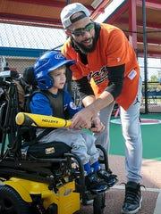 Boston Red Sox pitcher David Price assists Miracle League player Finn Switzer during a league game.