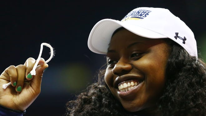 Arike Ogunbowale holds a piece of the net during Notre Dame's victory celebration after winning the women's Final Four.
